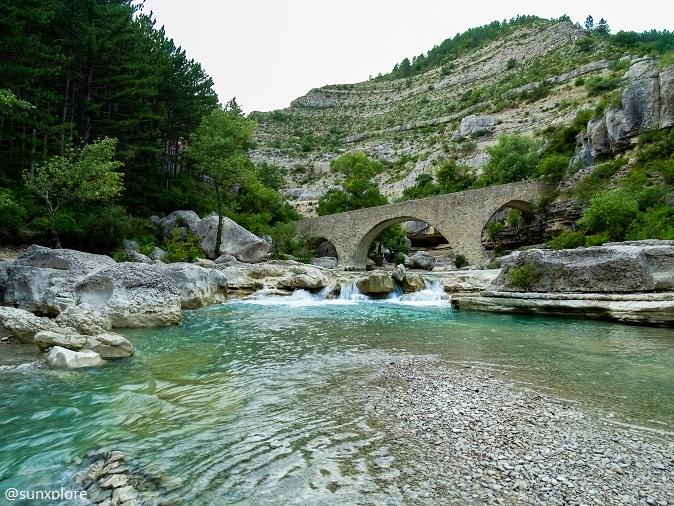 Une cascade s'écoule sous un pont roman dans les gorges de la méouge